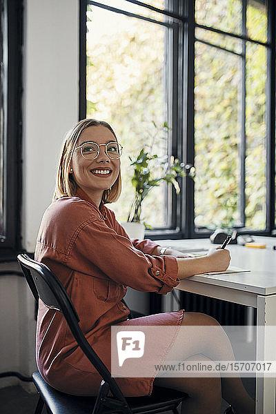 Porträt einer lächelnden Geschäftsfrau  die am Schreibtisch im Büro Notizen macht