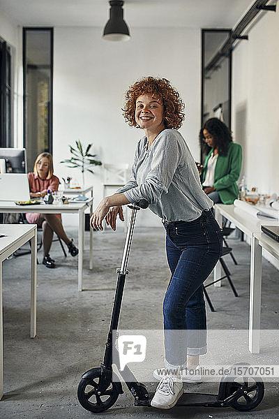 Porträt einer lächelnden Geschäftsfrau mit Kickroller im Amt