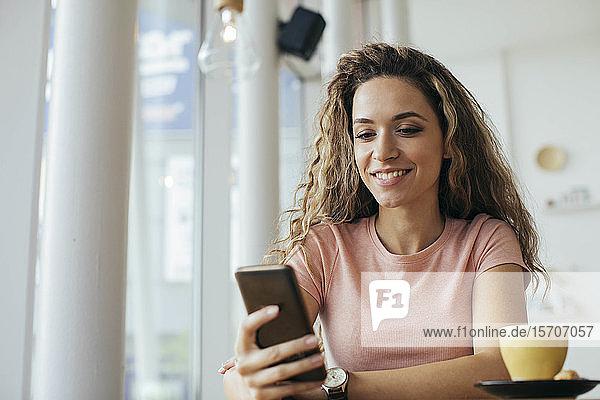 Junge Studentin schaut mit ihrem Smartphone in den Coffee Shop
