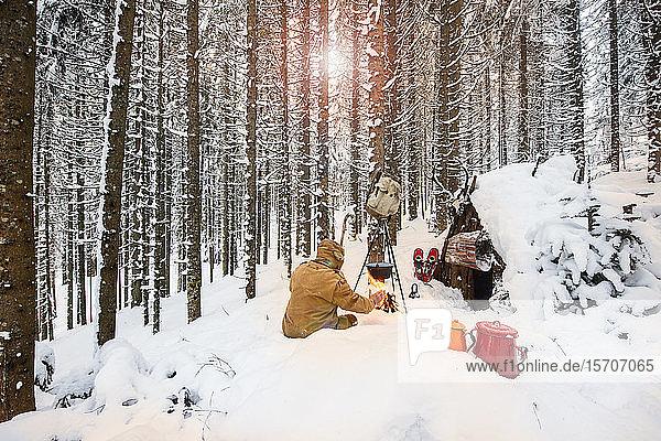Mann bereitet im Winterwald neben einem Holzunterstand Tee zu  Bundesland Salzburg  Österreich
