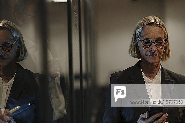 Reife Geschäftsfrau benutzt Smartphone in einem in einer Glasscheibe reflektierten Beamten