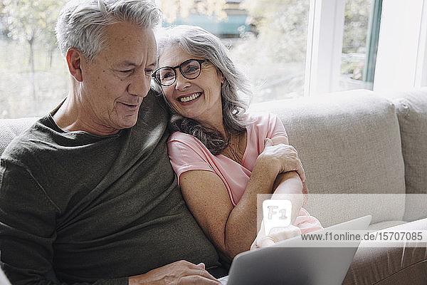 Glückliches älteres Ehepaar mit Laptop zu Hause auf der Couch