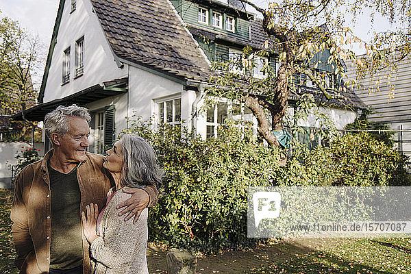 Älteres Ehepaar im Herbst im Garten ihres Hauses