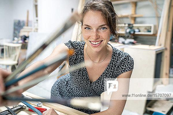 Junge Künstlerin steht in ihrem Atelier