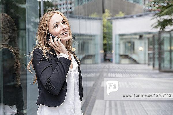 Lächelnde Geschäftsfrau am Telefon in der Stadt