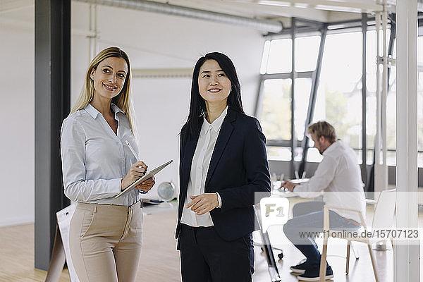 Zwei Geschäftsfrauen mit Tablett im Büro und Geschäftsmann im Hintergrund