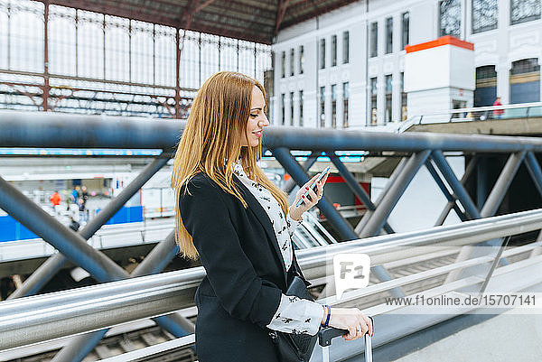 Junge Frau benutzt Mobiltelefon am Bahnhof