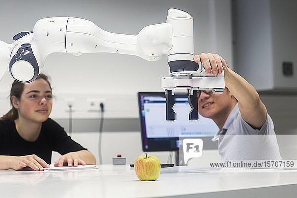 Studenten  die an einem Universitätsinstitut Robotik studieren und mit einem Apfel experimentieren