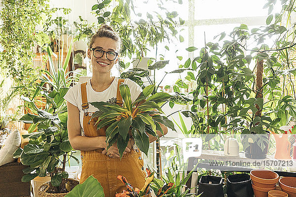 Portrait of a smiling young woman holding a plant in a small gardening shop
