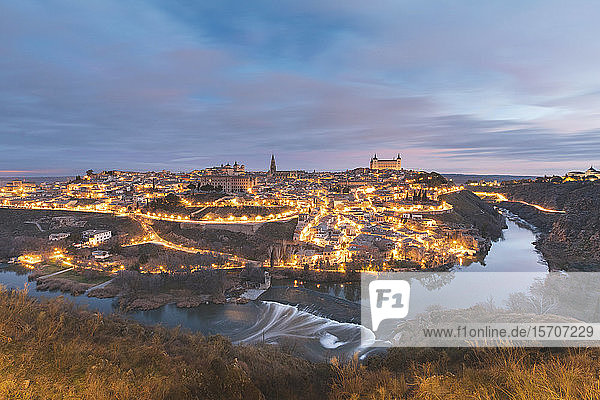 Spain Province of Toledo  Toledo  Tagus river and illuminated city at dawn