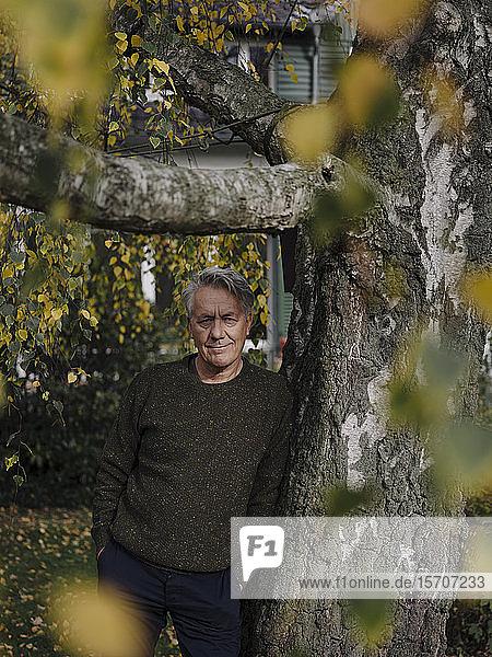 Portrait of a senior man at tree in garden