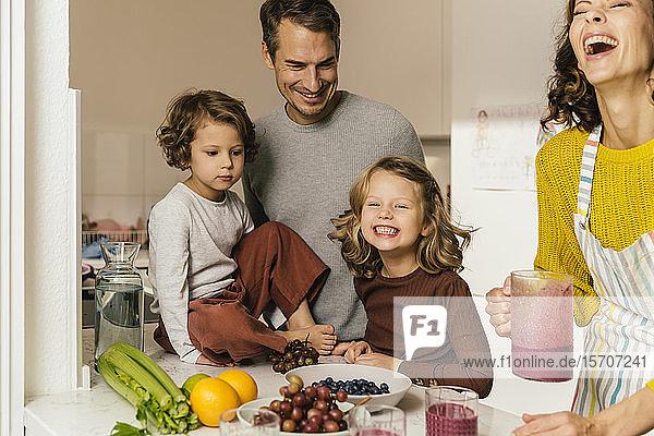 Glückliche Familie macht einen Smoothie in der Küche