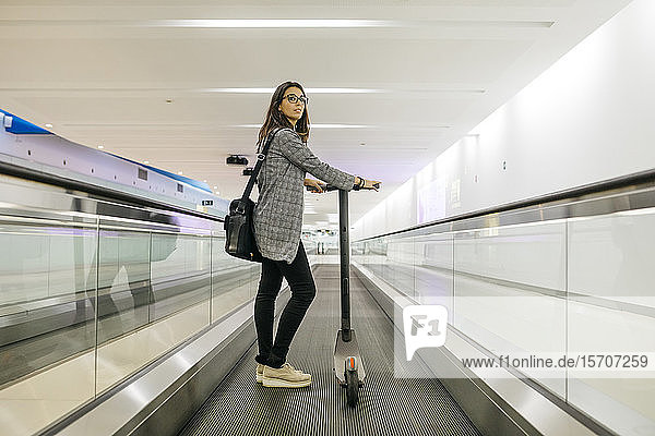 Businesswoman with her electric scooter on moving walkway