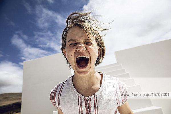 Mädchen mit windgepeitschtem Haar  schreit laut