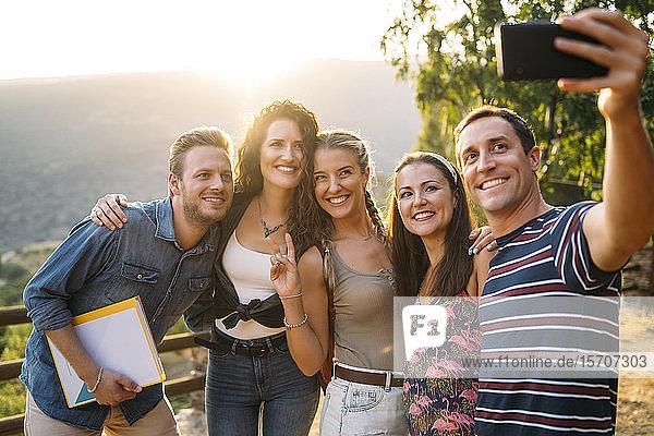 Happy friends taking a selfie in rural landscape