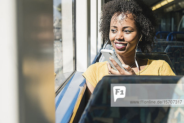 Lächelnde junge Frau mit Kopfhörern und Smartphone in einem Zug