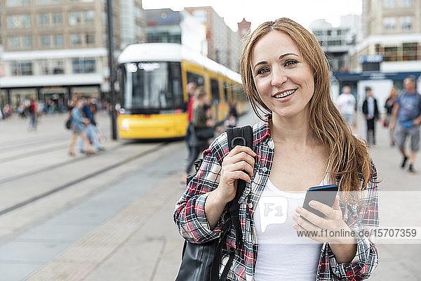 Porträt einer lächelnden Frau in der Stadt mit einer Straßenbahn im Hintergrund  Berlin  Deutschland