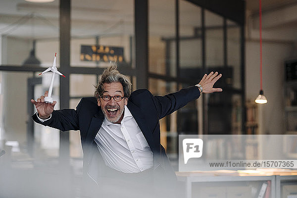 Excited senior businessman with wind turbine model in office