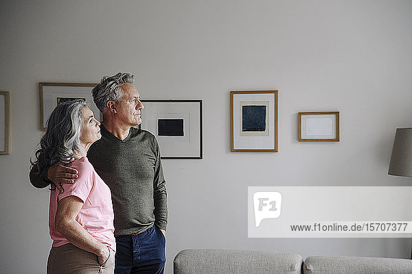 Senior couple standing in living room at home