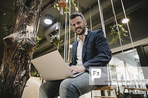 Geschäftsmann mit Laptop im Coworking Space,  auf der Schaukel sitzend