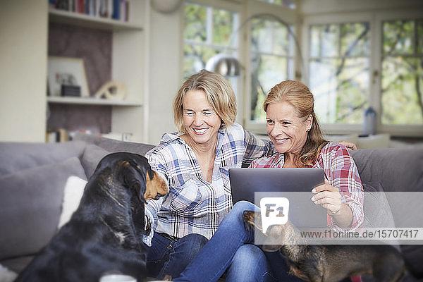 Zwei glückliche reife Frauen mit Hund und Laptop zu Hause