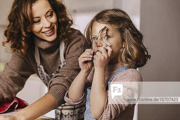 Playful girl with her mother holding Christmas cookie cutter in kitchen