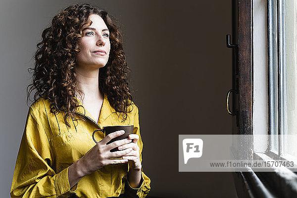 Frau schaut mit Kaffeetasse aus dem Fenster
