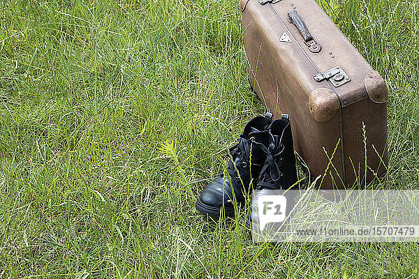 Old brown leather suitcase and pair of black boots on a meadow