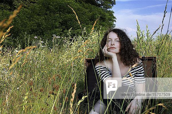 Porträt einer jungen Frau  die in einem Koffer auf einer Wiese sitzt