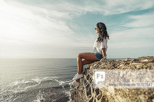Junge Frau sitzt auf einem Aussichtspunkt und schaut in die Ferne  Getxo  Spanien