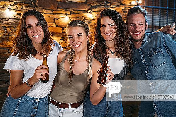 Gruppenporträt von glücklichen Freunden im Freien in einem Steinhaus bei einer Party
