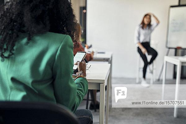 Geschäftsfrau benutzt Smartphone während eines Workshops im Konferenzraum