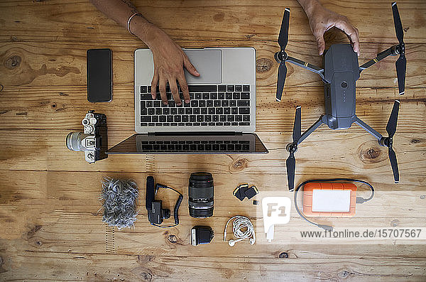 Person sitting at table with photografic equipment  using laptop  overhead view