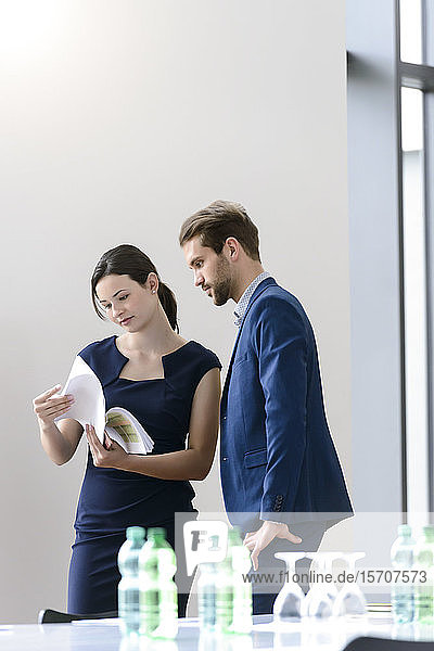 Businesswoman with colleague checking documents in office
