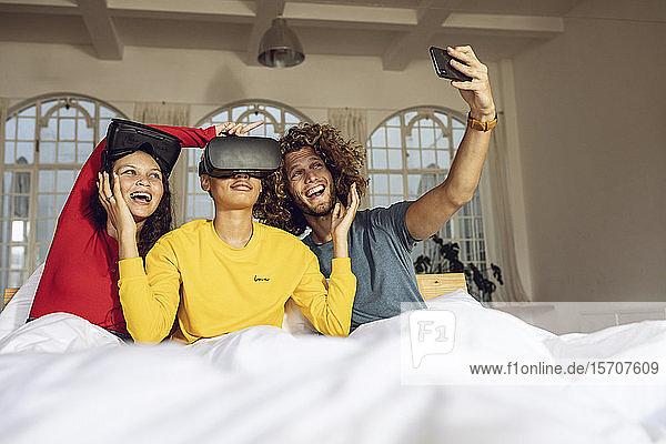 Glückliche Freunde  die zu Hause im Bett mit VR-Brille und Smartphone Spaß haben