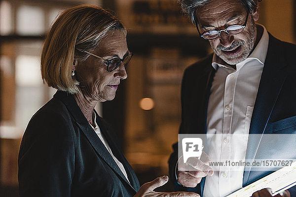 Geschäftsmann und Geschäftsfrau mit Tablet-Gespräch im Amt
