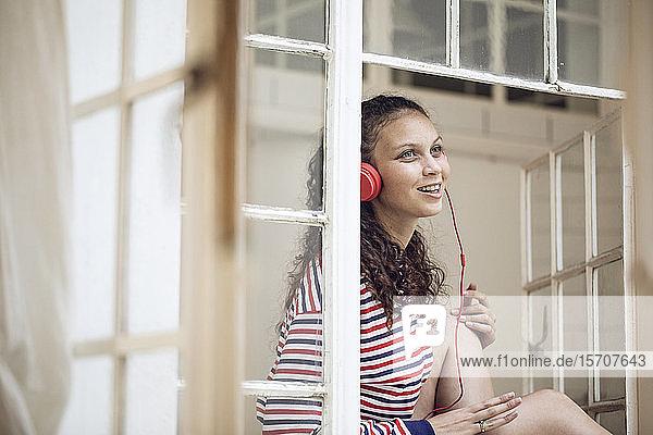 Glückliche junge Frau am Fenster  die Musik hört