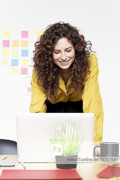 Lächelnde Frau arbeitet am Laptop am Schreibtisch im Büro