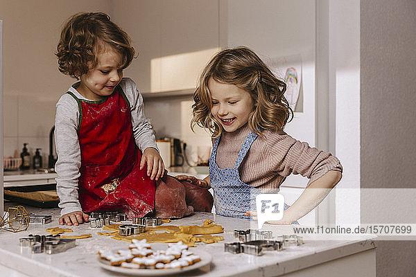 Zwei glückliche Mädchen bereiten in der Küche Weihnachtsplätzchen zu