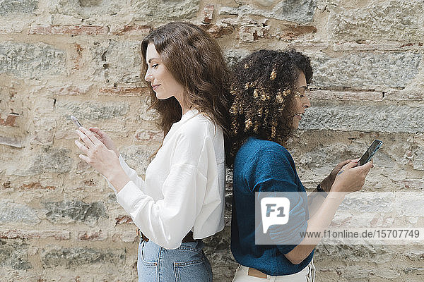 Two women standing back to back using smartphones