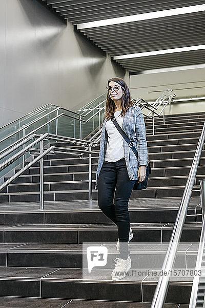Frau  die eine Treppe in einer U-Bahn-Station hinuntergeht  um zur Arbeit zu gehen.