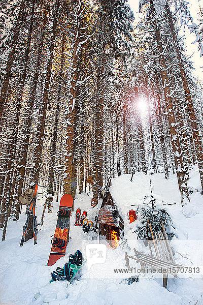 Österreich  Salzburg  Altenmarkt im Pongau  Wintersportgeräte liegen bei Sonnenuntergang vor verschneiter Waldhütte