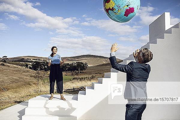 Geschäftsmann und -frau spielen mit aufblasbarem Globus