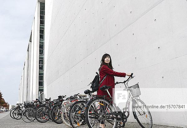 Geschäftsfrau mit Fahrrad im Hintergrund des modernen Gebäudes