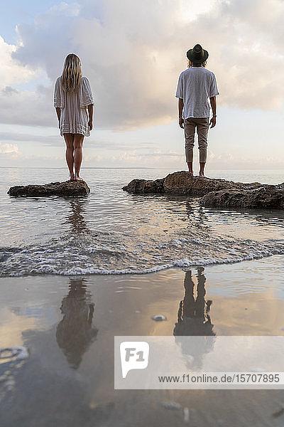 Rückenansicht eines jungen Paares  das auf Felsen vor dem Meer steht  Ibiza  Balearen  Spanien