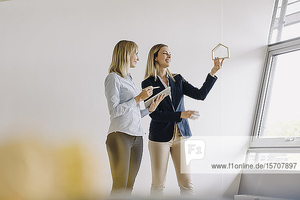 Two young businesswomen with tablet and house model talking in office