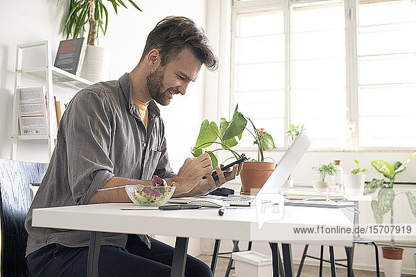 Smiling man using smartphone during lunch break at desk in office