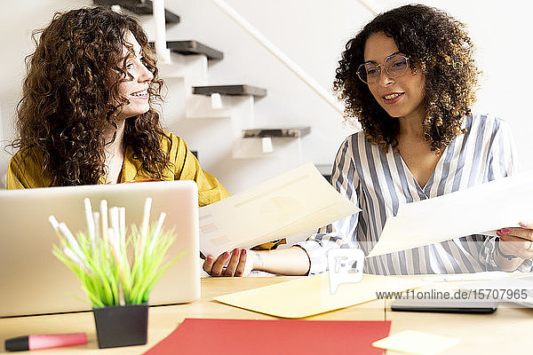 Zwei Frauen arbeiten gemeinsam an Papieren am Schreibtisch im Büro
