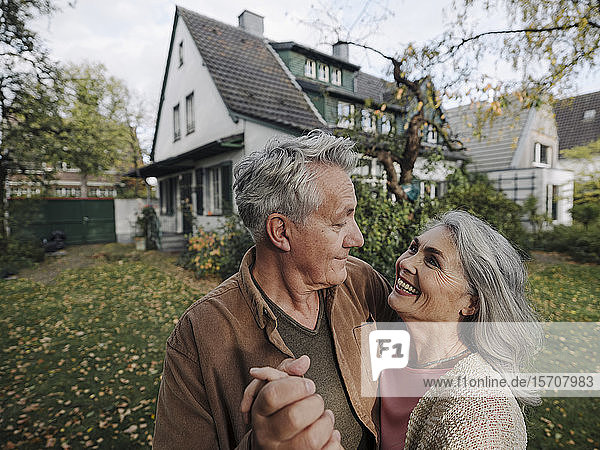 Happy senior couple in garden of their home in autumn