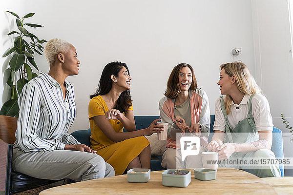Vier Frauen sitzen auf der Couch und unterhalten sich